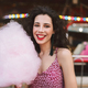 Smiling lady in dress eating cotton candy happily looking in camera spending time in amusement park - PhotoDune Item for Sale