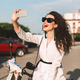 Young cheerful woman in suite and sunglasses sitting on moped happily taking selfie on city street - PhotoDune Item for Sale