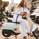 Pretty lady in white suite sitting on moped with coffee to go happily laughing in city center - PhotoDune Item for Sale