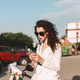 Stylish girl in suite and sunglasses sitting on moped thoughtfully using cellphone on city street - PhotoDune Item for Sale
