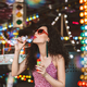 Young pretty lady in heart sunglasses and dress blowing bubbles spending time in amusement park - PhotoDune Item for Sale
