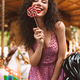 Smiling girl in dress holding lolly pop candy happily looking in camera in amusement park - PhotoDune Item for Sale