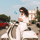 Pretty smiling lady in white suite and sunglasses sitting on moped using cellphone in city center - PhotoDune Item for Sale