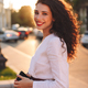 Beautiful smiling lady in white jacket on street joyfully looking in camera with cellphone in hands - PhotoDune Item for Sale