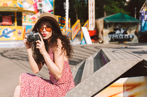 Beautiful lady in sunglasses and hat spending time in amusement park with little camera - Stock Photo - Images