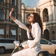 Smiling girl in white suite sitting on moped happily covering her face from sunlights in the city - PhotoDune Item for Sale