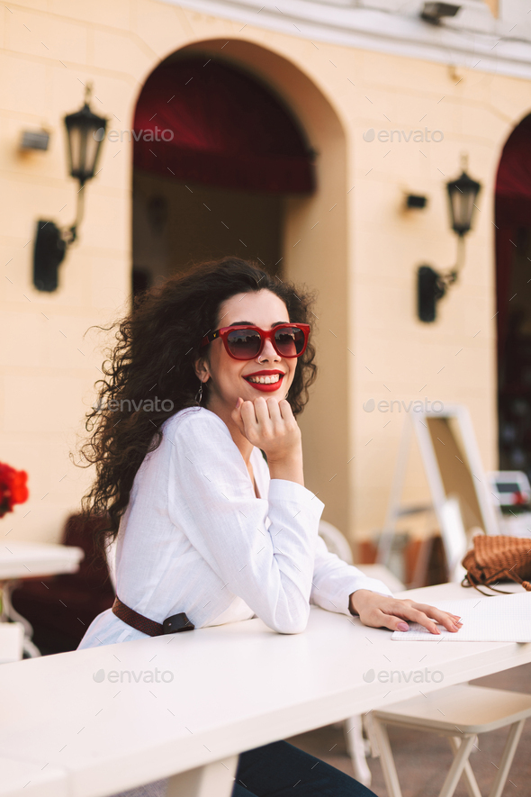 Beautiful smiling in sunglasses standing and happily looking in camera in summer terrace of cafe - Stock Photo - Images