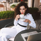 Beautiful lady in white suite drinking coffee dreamily looking in camera in street cafe - PhotoDune Item for Sale