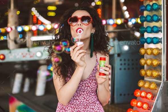 Beautiful lady in heart sunglasses and dress standing and blowing bubbles in amusement park - Stock Photo - Images