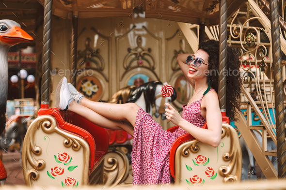 Joyful girl in sunglasses and dress holding lolly pop candy riding on carousel in amusement park - Stock Photo - Images
