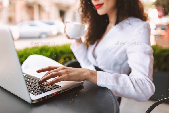 Woman body sitting at the table with cup of coffee in hand and laptop in cafe on street - Stock Photo - Images