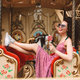 Joyful girl in sunglasses and dress holding lolly pop candy riding on carousel in amusement park - PhotoDune Item for Sale