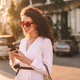 Beautiful smiling lady in sunglasses and white jacket happily using cellphone  standing on street - PhotoDune Item for Sale