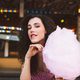 Beautiful lady in dress standing with cotton candy and dreamily looking in camera in amusement park - PhotoDune Item for Sale