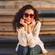 Beautiful girl in sunglasses and white jacket sitting on stairs on street happily looking in camera - PhotoDune Item for Sale