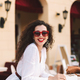 Cheerful lady with dark hair in sunglasses joyfully looking in camera in summer terrace of cafe - PhotoDune Item for Sale
