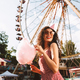 Happy girl in sunglasses and birthday cap eating cotton candy in amusement park over ferris wheel - PhotoDune Item for Sale