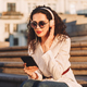 Pretty girl in sunglasses and white jacket sitting on stairs listening music in headphones on street - PhotoDune Item for Sale