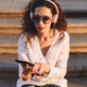 Beautiful lady in sunglasses sitting on stairs with cellphone listening music in headphones - PhotoDune Item for Sale