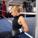 Female Boxer  Training In Gym Wearing Boxing Gloves Sitting On Boxing Ring - PhotoDune Item for Sale