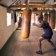 Action Shot Of Male Boxer In Gym Training With Leather Punch Bags - PhotoDune Item for Sale