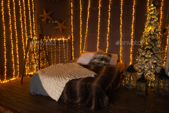 Cozy christmas bed with decor and lamps - Stock Photo - Images