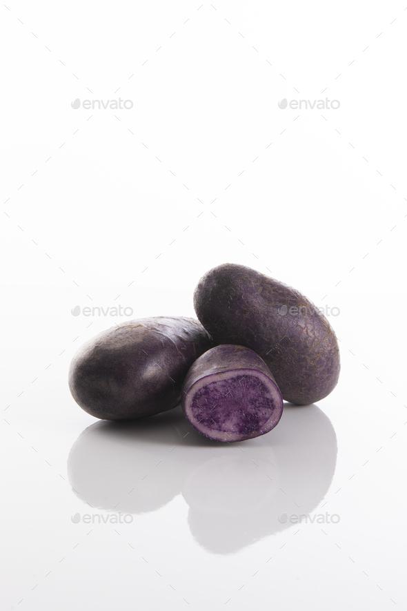 Purple potatoes with white background, Vitelotte noire - Stock Photo - Images