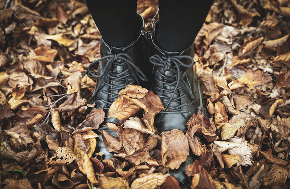 young woman feet with black boots in autumn leaves - Stock Photo - Images