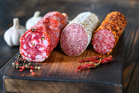 Assortment of salami on the wooden board - Stock Photo - Images