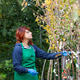 Young florist with red hair works in a nursery. - PhotoDune Item for Sale