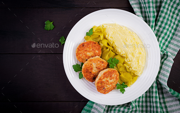 Homemade fried cutlets/meatballs with mashed potatoes and pickled cucumber on white plate. - Stock Photo - Images