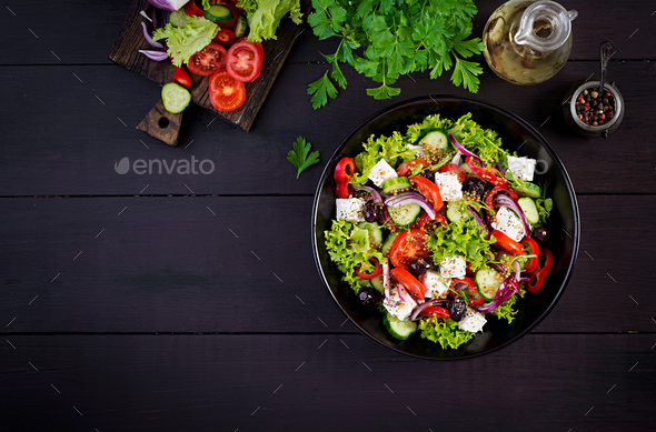 Greek salad with cucumber, tomato, sweet pepper, lettuce, red onion, feta cheese and olives. - Stock Photo - Images