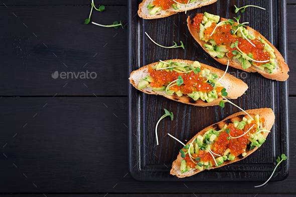 Sandwiches with salmon red caviar and salsa with avocado. - Stock Photo - Images