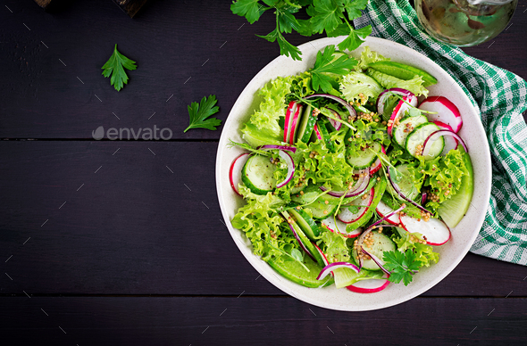 Healthy vegan food. Vegetarian vegetable salad of radish, cucumbers, lettuce  and red onion. - Stock Photo - Images