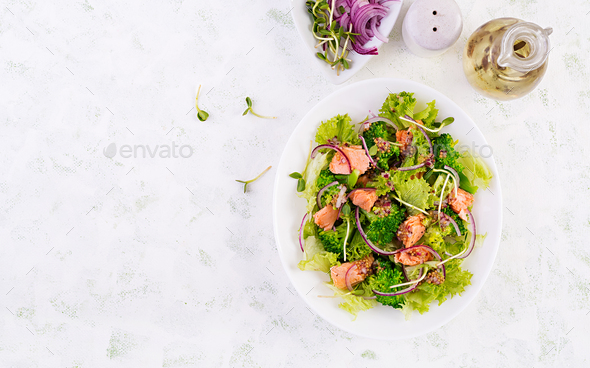 Salad of baked fish salmon, broccoli, lettuce, red onion and dressing. - Stock Photo - Images
