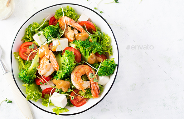Delicious fresh salad with shrimps / prawns, broccoli, feta cheese, tomatoes, lettuce - Stock Photo - Images