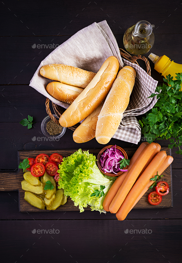 Ingredients for hot dog with  sausage, pickled cucumber, tomatoes, red onions - Stock Photo - Images