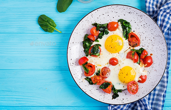Breakfast. Ketogenic diet food. Fried egg, spinach, and tomatoes. - Stock Photo - Images