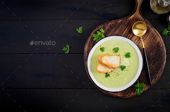 Homemade broccoli cream soup with croutons in white bowl on wooden board. - Stock Photo - Images