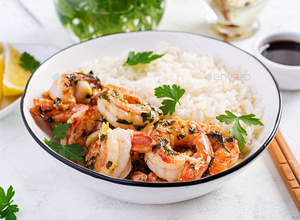 Grilled shrimps and boiled rice. King prawn tails in orange-garlic sauce with parsley. - Stock Photo - Images