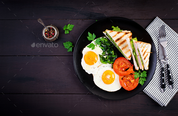 Breakfast: fried egg, spinach, tomatoes and club sandwich on plate. Top view, copy space - Stock Photo - Images