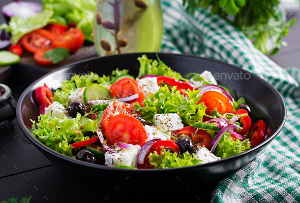 Healthy food. Greek salad with cucumber, tomato, sweet pepper, lettuce, red onion, feta cheese - Stock Photo - Images