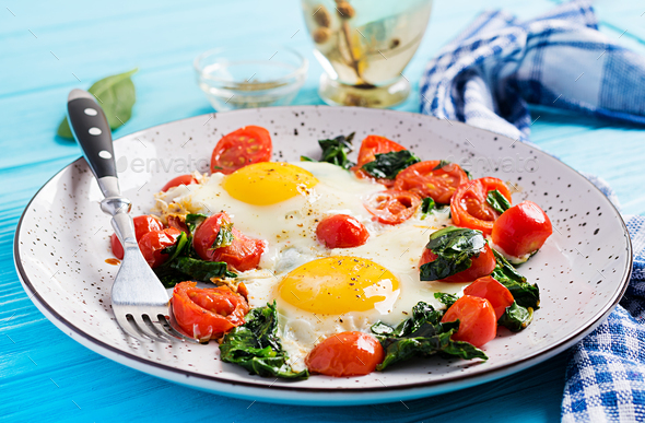 Plate with a keto diet food. Fried egg, spinach, and tomatoes. Keto, paleo breakfast. - Stock Photo - Images