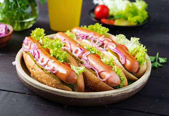 Hot dog with  sausage, pickled cucumber, tomatoes, red onions and lettuce - Stock Photo - Images