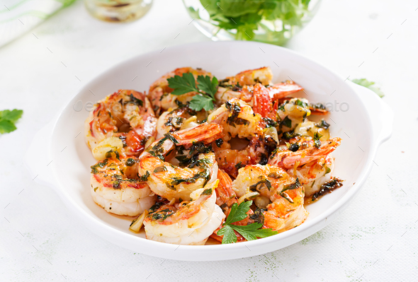 Grilled shrimps. King prawn tails in orange-garlic sauce with parsley. - Stock Photo - Images