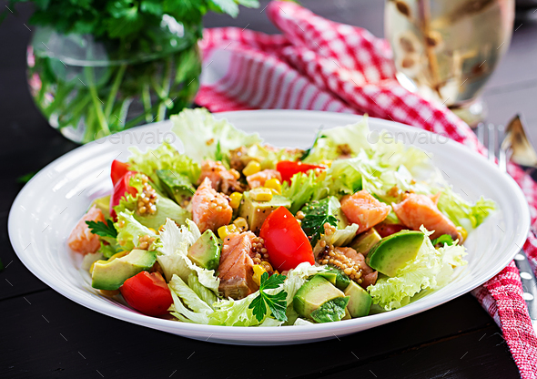 Salad with grilled salmon, lettuce, avocado, tomatoes and corn on a white bowl. Paleo diet. - Stock Photo - Images