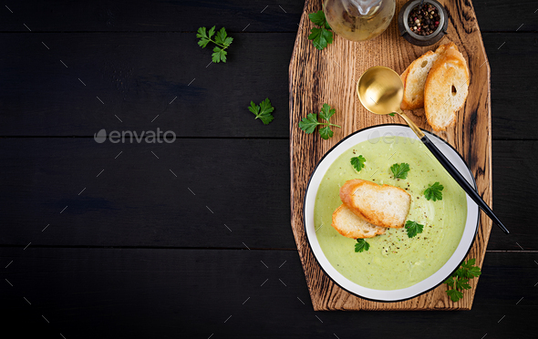 Homemade broccoli cream soup with croutons in white bowl on wooden board - Stock Photo - Images