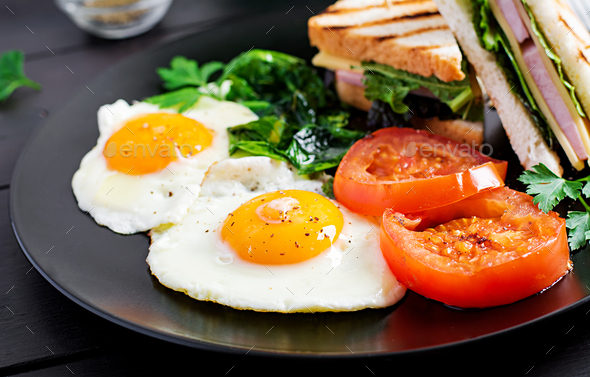 Breakfast: fried egg, spinach, tomatoes and club sandwich on plate. - Stock Photo - Images