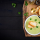 Homemade broccoli cream soup with croutons in white bowl on wooden board - PhotoDune Item for Sale