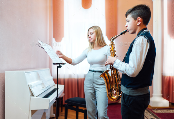 teacher turns over sheet of sheet music for student in saxophone lesson - Stock Photo - Images
